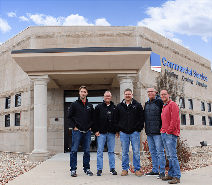 commercial service team standing in front of building
