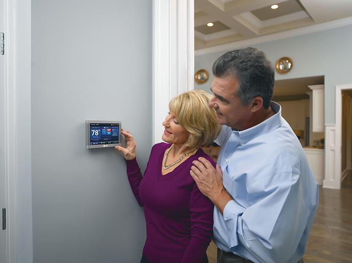 couple adjusting thermostat